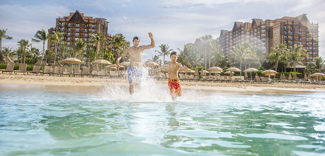 Family on beach at Aulani Disney Resort