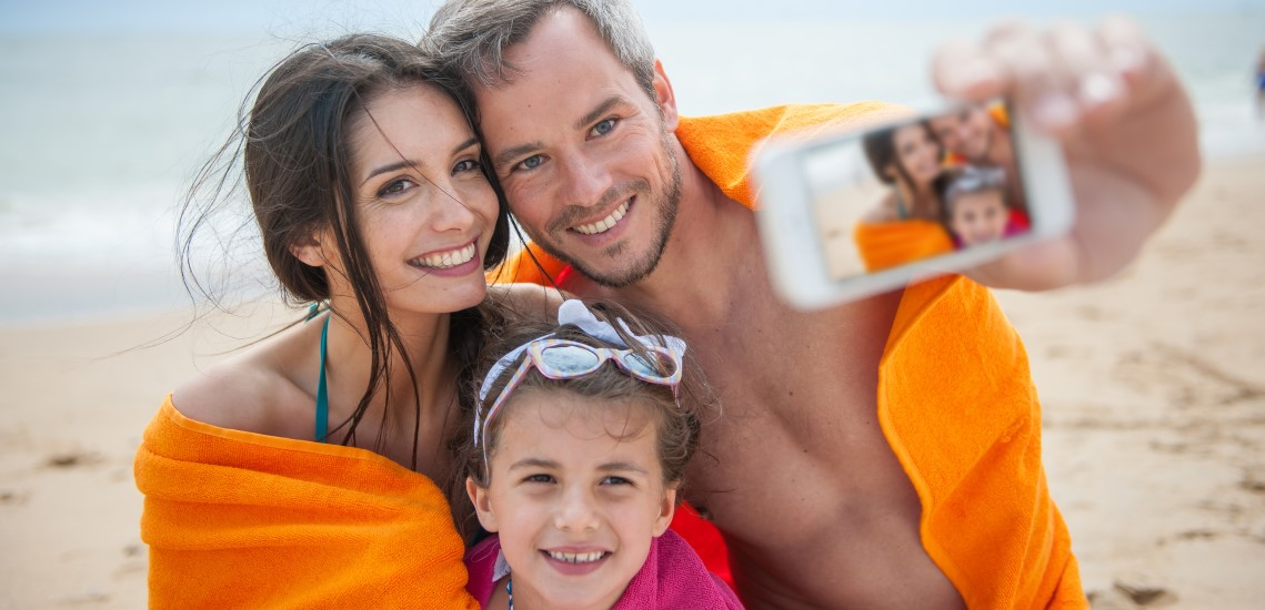 Family on beach taking a selfie