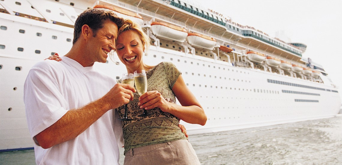 ouple toasting in front of cruise ship