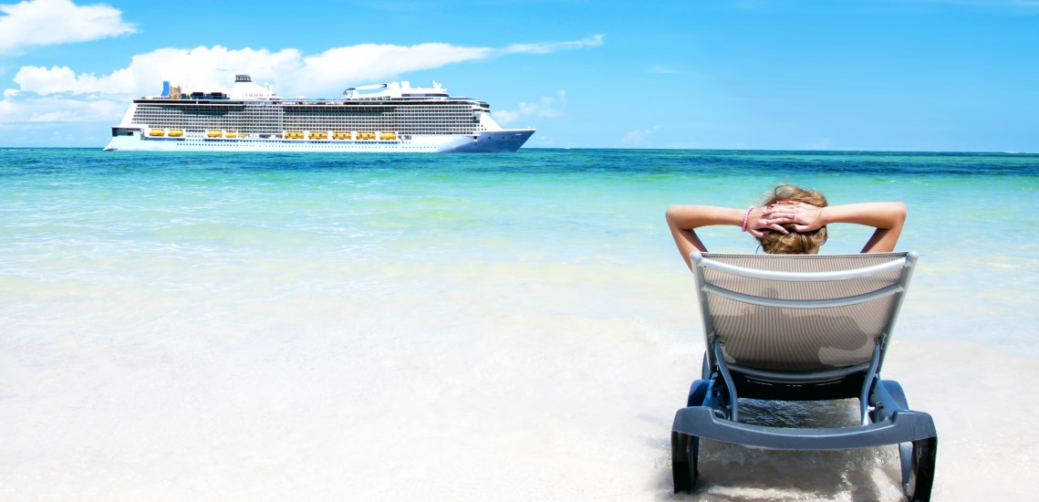 Cruise ship passing by woman lounging on beach