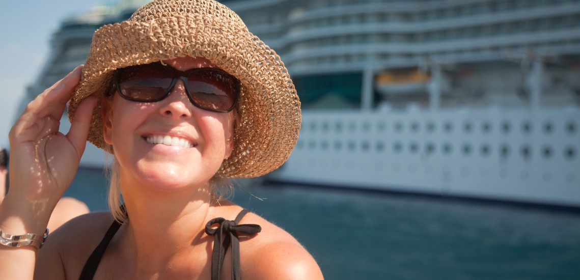 Lady in hat in front of cruise ship