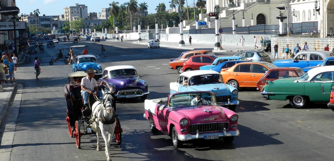 Old Styler cars and horse and buggy on streets of Havana, Cuba.