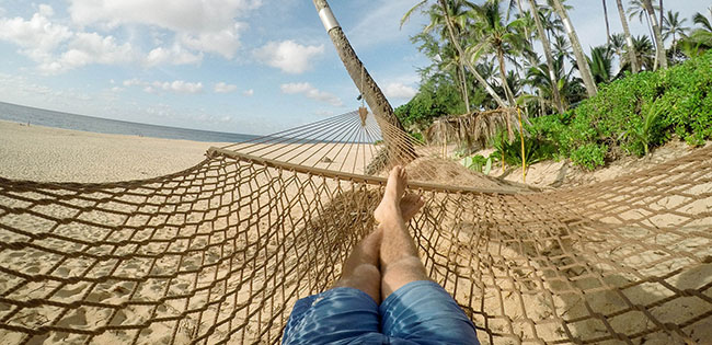 Person in hammock on beach.