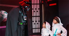 Darth Vadar character greets child.